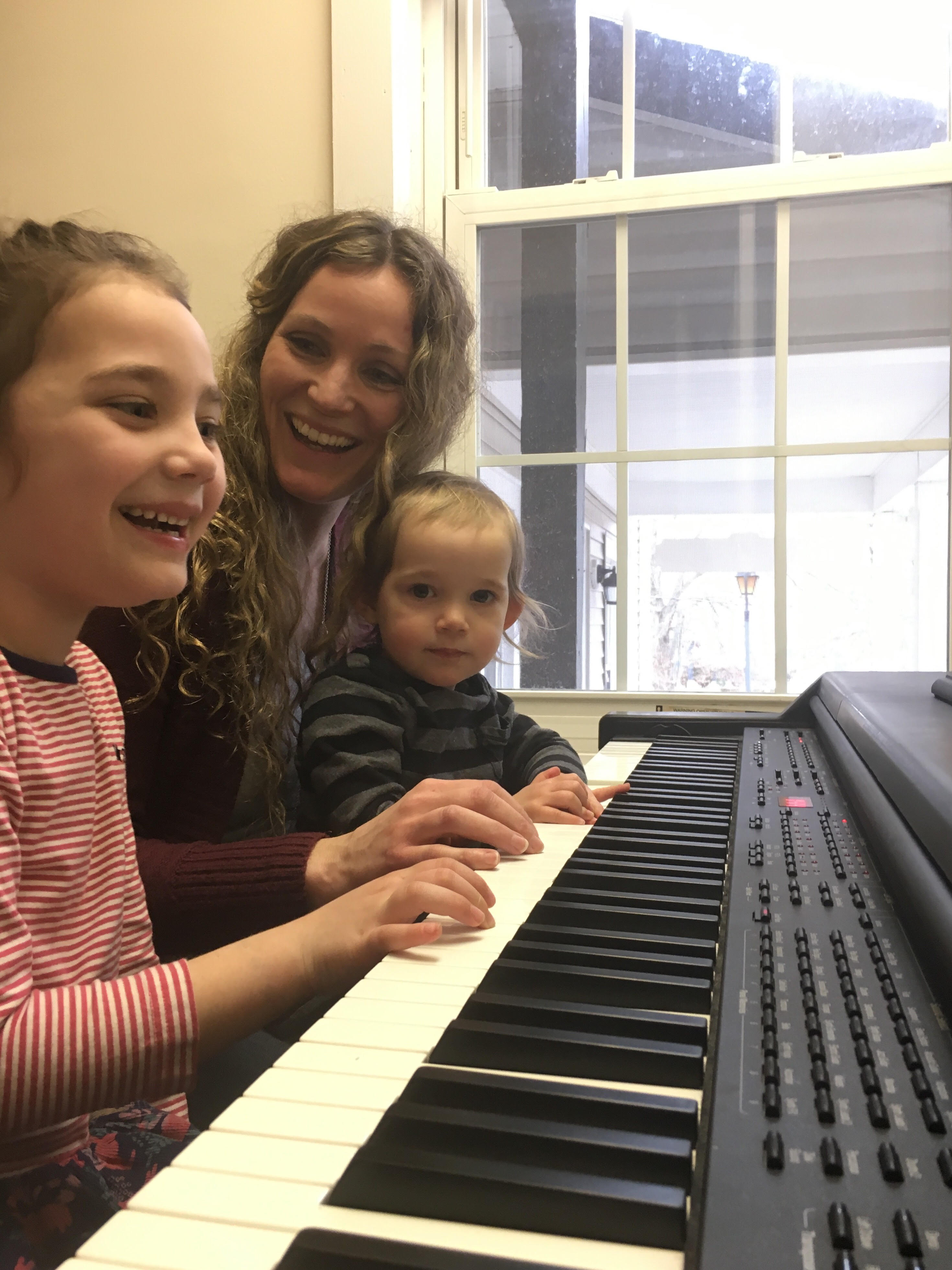 mother and two children playing piano